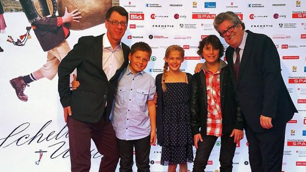 Zwei Männer posieren zusammen mit drei Kindern vor dem Schellen-Ursli-Filmplakat.