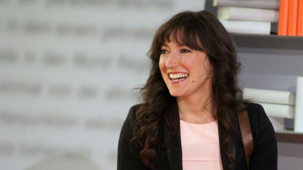 Farbige Portätaufnahme von der lachenden Charlotte Roche
