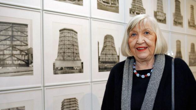 Farbige Portätaufnahme von Hilla Becher vor gerahmten Fotos an einer Wand.