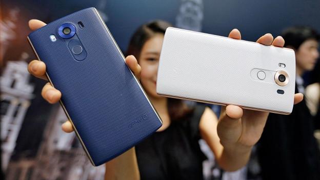 Eine Asiatin haltet ein blaues und ein weisses Smartphone in die Kamera.
