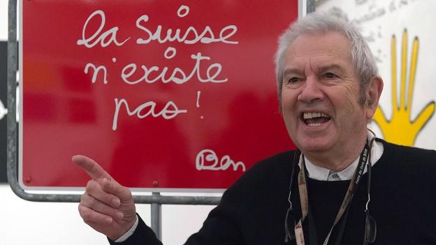 Farbige Portätaufnahme von Ben Vautier vor einer Tafel mit der Aufschrift «La Suisse n'existe pas».