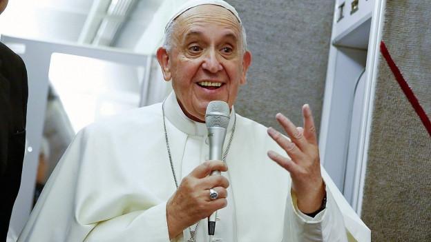 Farbige Porträtaufnahme von Papst Franzikus mit Mikrofon.