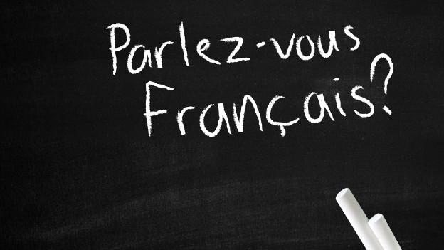 """Auf einer Wandtafel steht mit weisser Kreide geschrieben: """"Parlez-vous Francais?""""."""