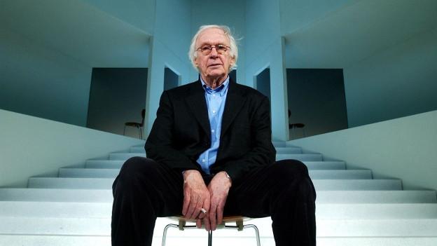 Ein älterer Herr sitzt auf einem Stuhl, in einem schwarzen Anzug, hellblaues Hemd.