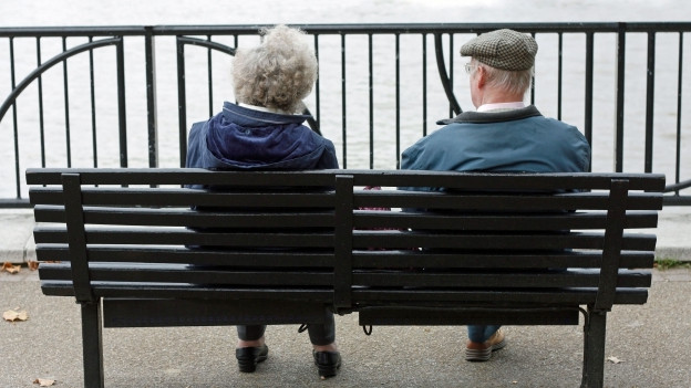 Eine ältere Frau und ein älterer Mann sitzen auf einer Bank.
