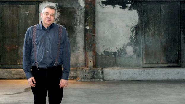 Ein Mann mit dunkler Kleidung steht in einer alten Fabrikhalle.