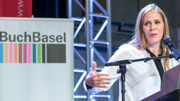 Eine blonde Frau mit einer weissen Bluse steht am Rednerpult und spricht ins Mikrophon.