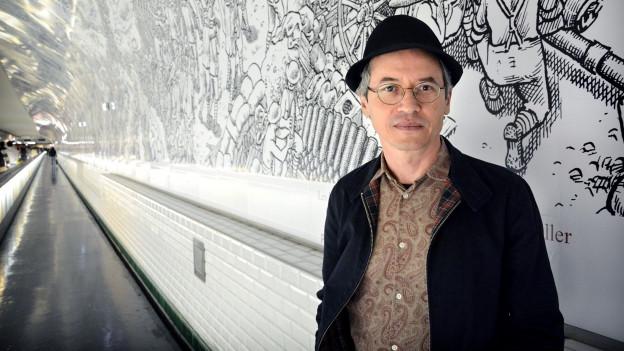 Ein Mann mit Hut und Brille steht in einem langen Gang, der mit einer Schwarz-Weiss-Zeichnung bemalt ist.
