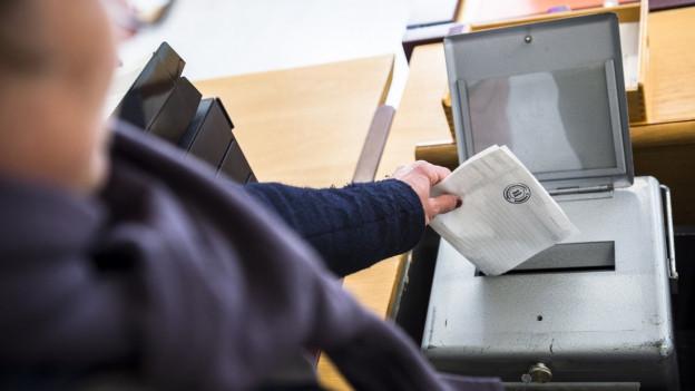 Eine Person wirf einen Abstimmungszettel in die Urne.