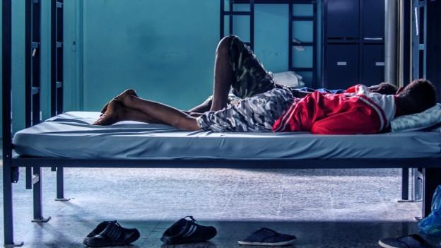 Zwei Männer liegen auf einem Bett und schlafen.