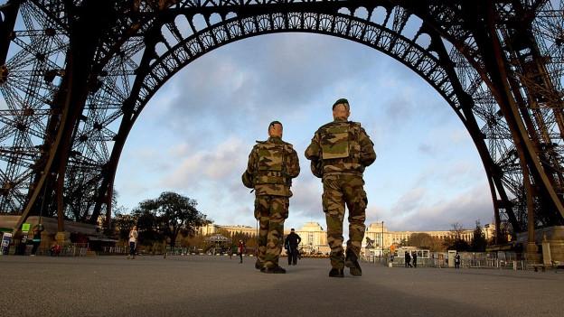 Zwei Soldaten unter dem Eiffelturm in Paris.
