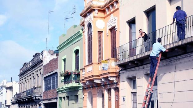 Eine Häuserwand: Auf der rechten Seite stehen zwei Personen auf einem Balkon und eine dritte steht auf einer Leiter.