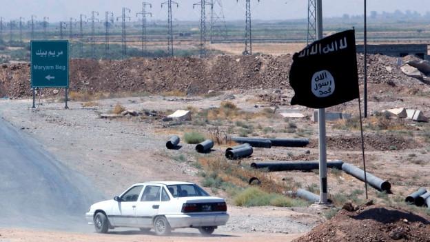Ein auto fährt an einer schwarzen Flagge mit arabischen Schriftzeichen vorbei.