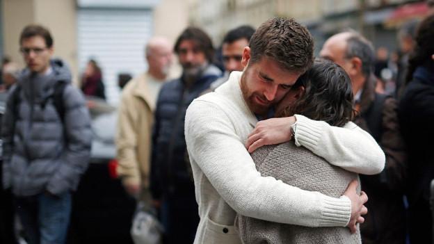 Zwei trauernde Menschen umarmen sich.