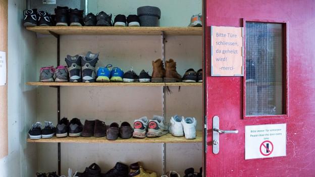 Blick auf ein Schuhregal und eine rote, geöffnete Türe.
