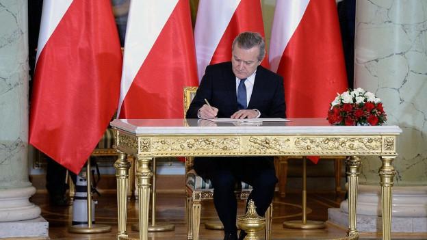Ein Mann sitzt vor polnischen Fahnen hinter einem goldenen Tisch.