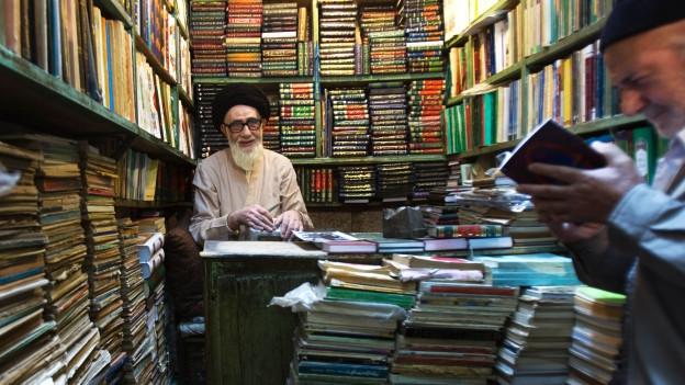 Zwei Männer in einem Raum voller Bücher