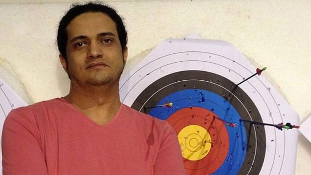 Farbiges Porträt von Ashraf Fayadh vor einer Dartscheibe.