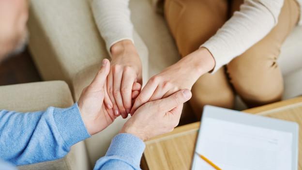 Ein Mann und eine Frau halten sich gegenseitig an den Händen.