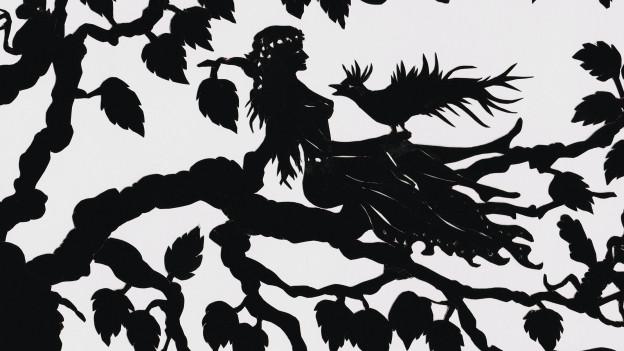 Der Scherenschnitt zeigt eine sitzende Frau mit Vogel.