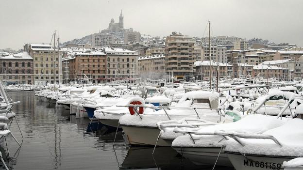 Schneebedeckte Boote im Hafen von Marseille.
