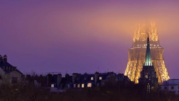 Ein Foto des Eiffelturms, der im Nebel verschwindet.