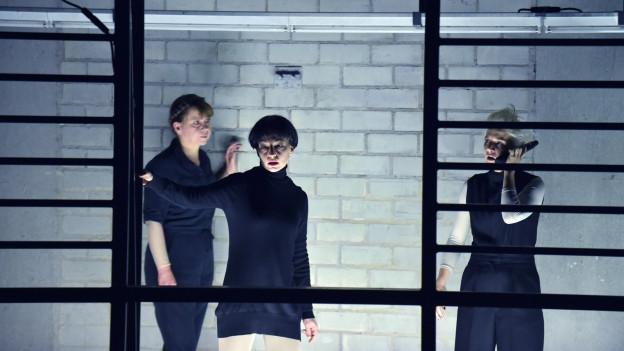 Drei Frauen in schwarzer Kleidung stehen vor einer blanken Backsteinwand.