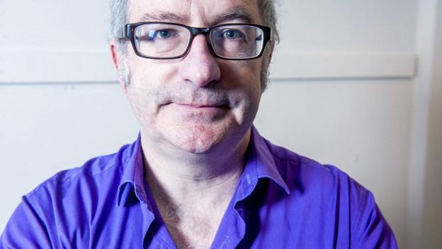 Frontalansicht auf einen Mann mit violettem Hemd und Brille.