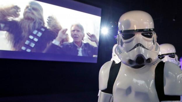 Ein Roboter steht vor einer Kinoleinwand – darauf: Harrison Ford im neuen «Star Wars».