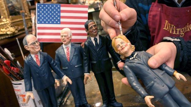 Vier Figuren von amerikanischen Politikern. Jemand hält eine Figur in der Hand und bemalt sie mit einem Pinsel.