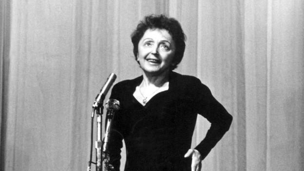 Eine ältere Frau steht vor einem Mikrofon.