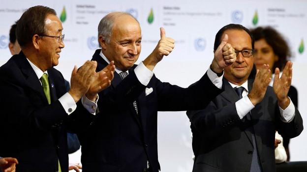 Drei Männer in dunklen Anzügen klatschen in die Hände.