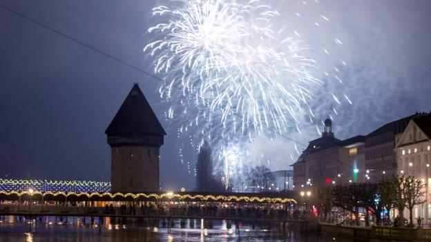 Eine beleuchtete Brücke, die über einen Fluss führt. Am Himmel kann man ein Feuerwerk erkennen.