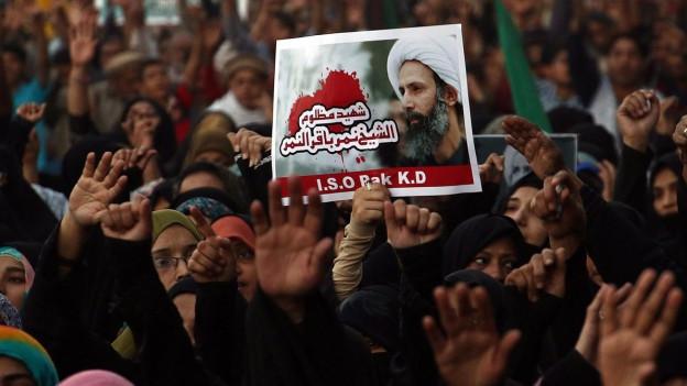 Demonstranten halten ein Bild des hingerichteten Geistlichen Nimr al-Nimr in die Höhe.