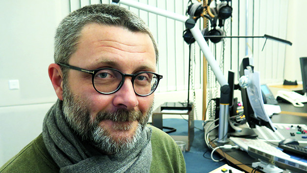 Ein Mann mit raspelkurzem Haar und Brille sitzt im Radiostudio.