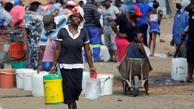 Farbige Frau trägt einen Wasserbehälter.