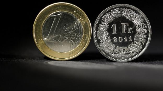 Ein Einfränkler und eine Euromünze.