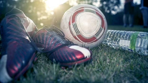 Ein Fussball, Fussballschuhe und eine Wasserflasche liegen im Rasen.