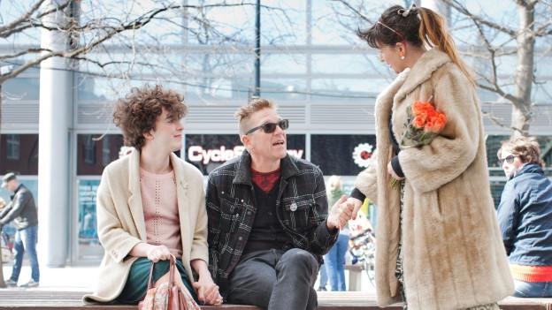 Drei Personen sitzen auf bzw. stehen vor einer Bank.