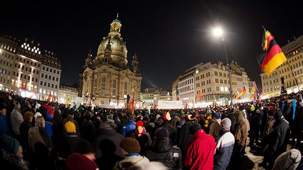 Denonstranten mit Deutschland-Fahnen vor der Frauenkirche in Dresden.