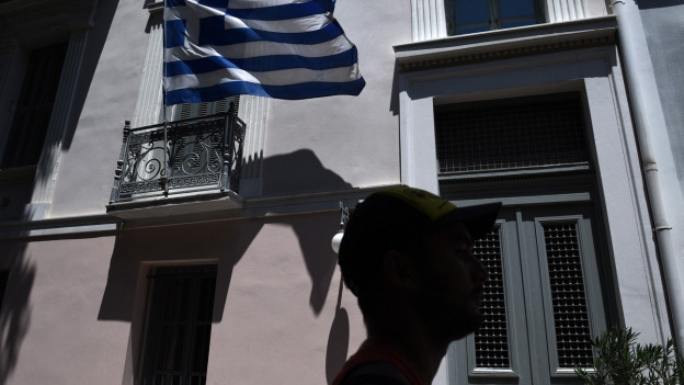 Griechenlandfahne, davor ein Mann im Gegenlicht.