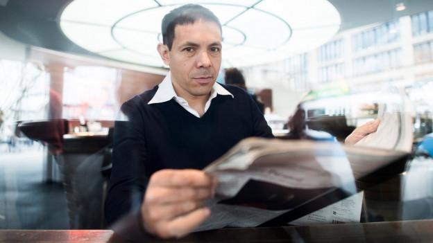 Porträt Bruno Ziauddin, der von einer Zeitung aufschaut.