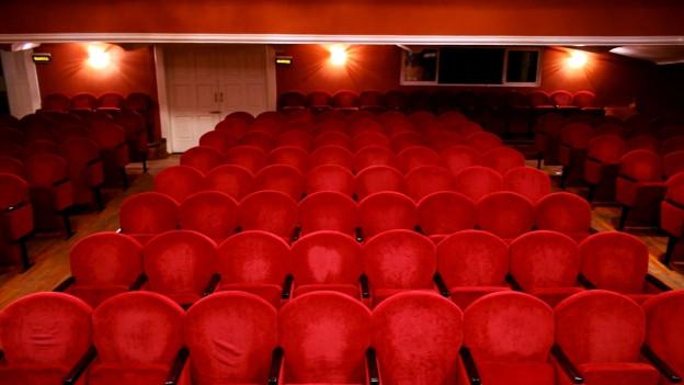Saal mit roten Polsterstühlen, die in Reihen stehen.