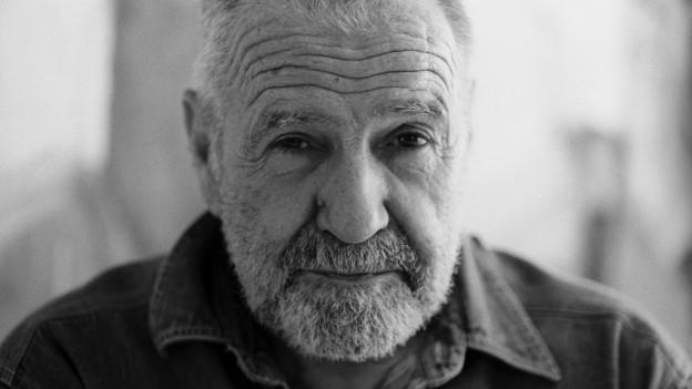 Ein älterer Herr mit Falten auf der Stirn und Bart.