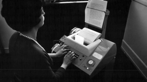 Eine Frau bedient ein Telex.