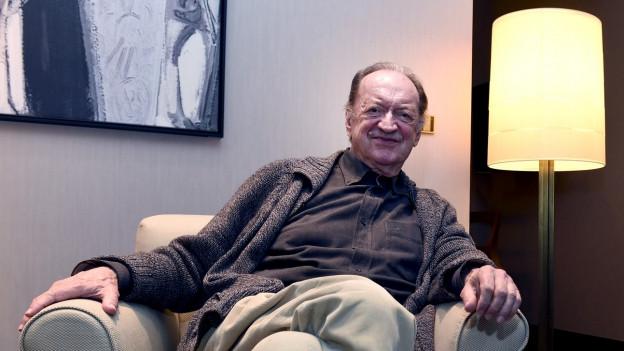 Ein älterer Herr sitzt auf einem Sessel und lächelt in die Kamera.