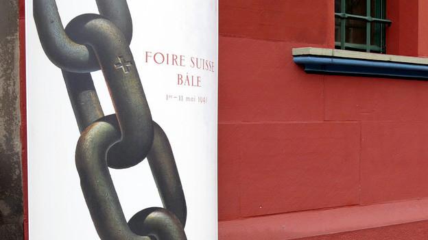 Ein Plakat der Mustermesse Basel vor einer Gebäudewand.