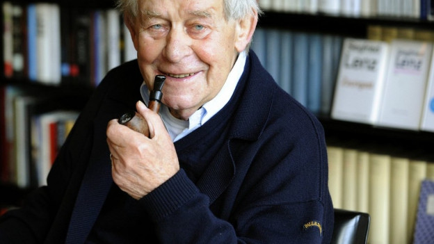 Ein älterer Herr sitzt vor einem Bücherregal.