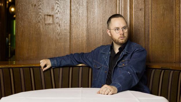 Ein junger Mann sitzt am Tisch in einem Kaffeehaus.