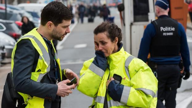 Zwei Flughafenangestellte in einer gelben Weste. Sie sind am Flughafen von Brüssel.